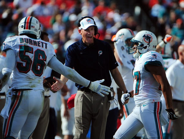 Miami Dolphins coach Joe Philbin celebrates with Kevin Burnett, left, and Jimy Wilson after they stopped the Buffalo Billsdrive during the fourth quarter, Sunday, Dec. 23, 2012, at Sun Life Stadium in Miami Gardens.