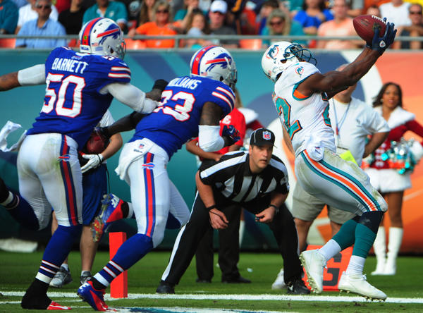 Miami Dolphins Reggie Bush catches his third touchdown of the day past the Buffalo Bills Nick Barnett, left and Kyle Williams during the third quarter, Sunday, Dec. 23, 2012, at Sun Life Stadium in Miami Gardens.