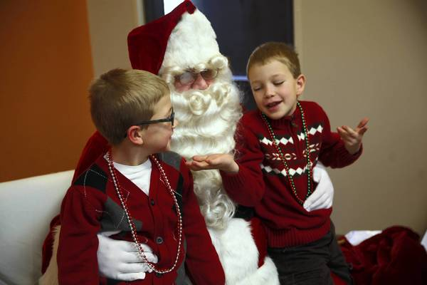 The Santa Claus at St. Teresa of Avila Catholic Church in Chicago not only asks the Anderson brothers Quinn, 9, left and Cal, 7, what they want for Christmas, but he also asks them if they know the story of Christmas.