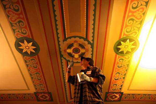 Joe Nicoletti applies the final touches of gold leaf to a frieze on the ceiling of City Hall's Main Street lobby originally painted more than 80 years ago. He first restored it 18 years ago.
