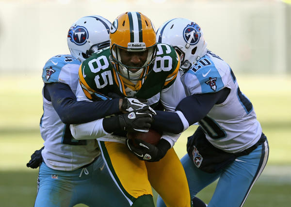 Greg Jennings #85 of the Green Bay Packers hangs onto the ball as he is hit by Coty Sensabaugh #24 (L) and Alterraun Verner #20 of the Tennessee Titans at Lambeau Field on December 23, 2012 in Green Bay, Wisconsin. The Packers defeated the Titans 55–7.