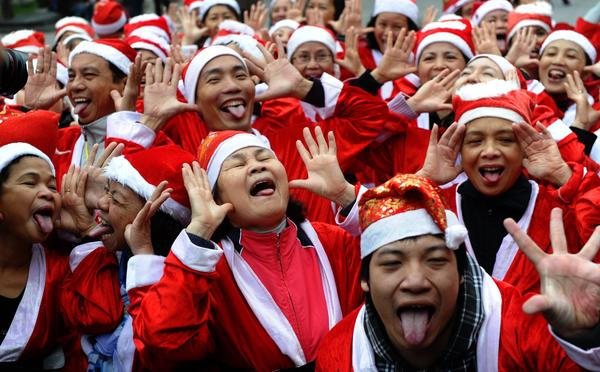 Members of a local Smiling Yoga club wearing Santa Claus costumes perform at a public park in Hanoi on December 23, 2012. Churches, shops, restaurants and shopping mails are decorated in the Southeast Asian nation with some six million catholics preparing to celebrate Christmas.