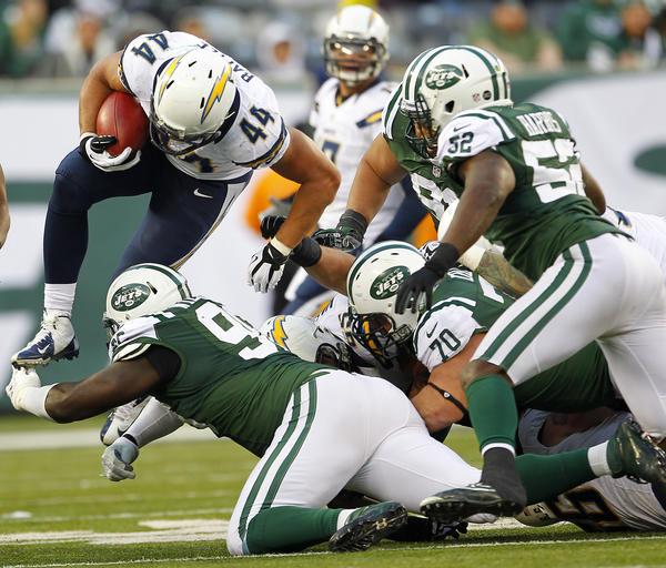 Running back Jackie Battle #44 of the San Diego Chargers leaps over Muhammad Wilkerson #96 of the New York Jets during the second half at MetLife Stadium on December 23, 2012 in East Rutherford, New Jersey. The Chargers defeated the Jets 27–17.