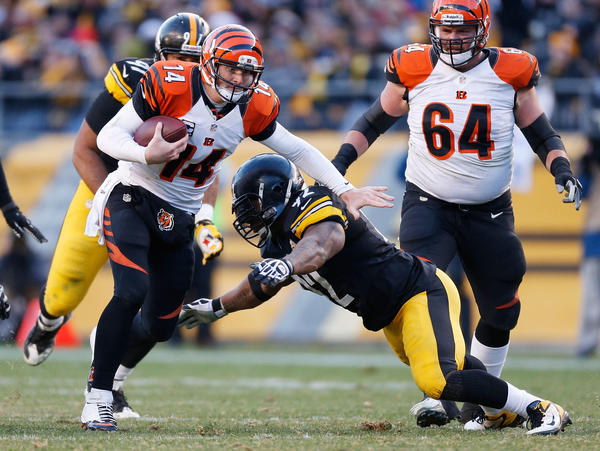 Andy Dalton #14 of the Cincinnati Bengals tries to get around the tackle of James Harrison #92 of the Pittsburgh Steelers during the fourth quarter at Heinz Field on December 23, 2012 in Pittsburgh, Pennsylvania. Cincinnati won the game 13–10.