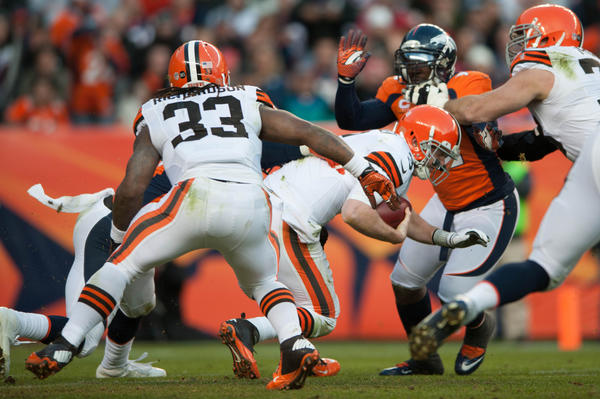 Quarterback Brandon Weeden #3 of the Cleveland Browns is sacked by outside linebacker Von Miller #58 of the Denver Broncos (obscured) and forced out of the game due to an injury at Sports Authority Field Field at Mile High on December 23, 2012 in Denver, Colorado. The Broncos defeated the Browns 34–12.
