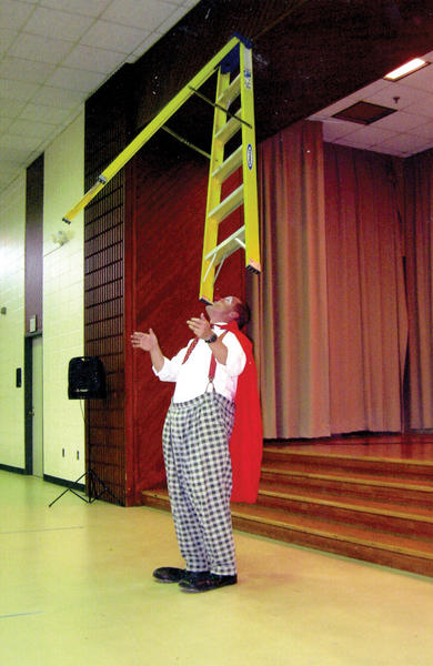 Kevin The Klown balances a ladder in his mouth at the Tri-State Civitan Club's Christmas variety show at the Potomac Center on Marshall Street in Hagerstown.