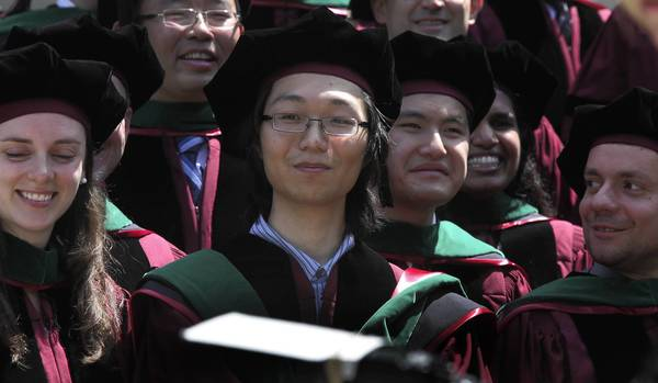 Sho Yano, center, poses for a class photo on June 8, 2012, at the University of Chicago. Yano is the youngest student to receive an M.D. and PhD in U. of C. history.