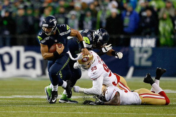 Russell Wilson #3 of the Seattle Seahawks runs with the ball in the firsy half against the San Francisco 49ers at Qwest Field on December 23, 2012 in Seattle, Washington. Seattle won 42–13.