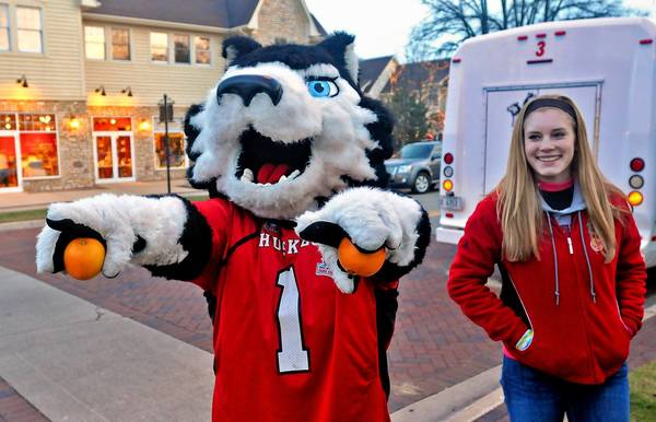 NIU student Lauren Boddy of Lily Lake and mascot Victor E. Huskie hand out oranges during an all-day tour to whip up excitement over NIU's appearance in the Orange Bowl.