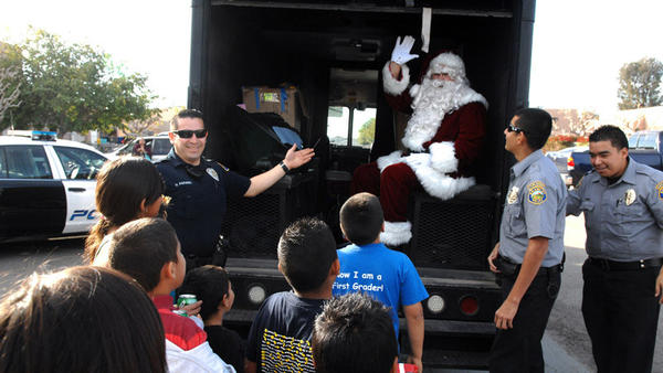 Santa Claus says hello to children at the Bike and Toy giveaway by Las Chabelas and the Brawley Police Department in Brawley on Sunday morning.