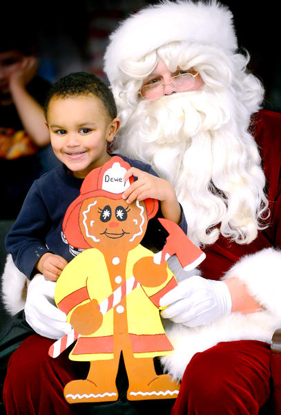 Dewey Woods, 3, holds a gingerbread firefighter as he sits with Santa Claus on Sunday night at the Clear Spring Volunteer Fire Co. activities building. Dewey and his family were burned out of their Big Pool home Saturday and already have found a new place to live. They received gifts and cash from around the Tri-State area and beyond.