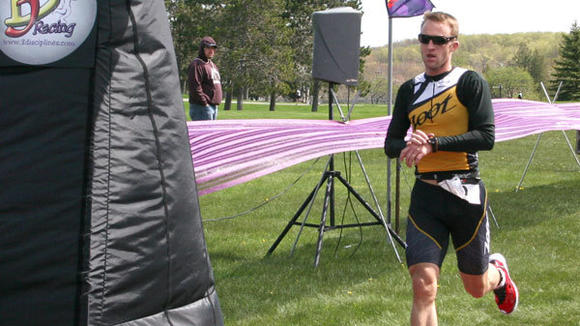 DAVE SMITH, a 2002 St. Mary grad, has never left the sports world and currently participates in duathlons and triathlons across the state. Smith is seen here crossing the finish line in first place at the 2011 Starkermann duathlon in Gaylord.