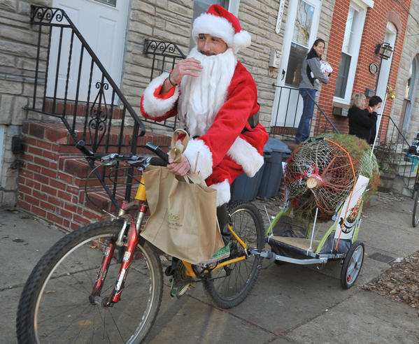 Jason Toraldo, followed by his two Santa's helpers, takes off from his S. Charles Street  home in Federal Hill to make a Christmas tree delivery to Locust Point. Jason Toraldo started a business called Pork-n-Pine,  to deliver Christmas trees and pulled pork sandwiches,  and for  local deliveries, he travels by bicycle.