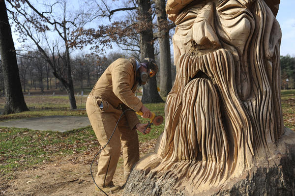 Chainsaw sculptor Mark Acton works on sanding a Druid sculpture in Druid Hill park.  It is carved in oak.
