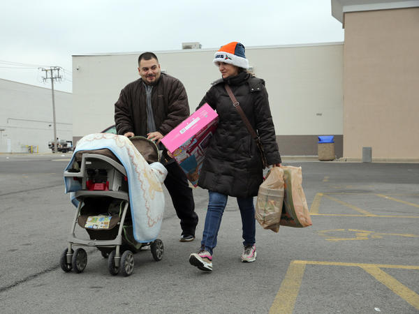 Sam, left, and Rocio Garcia, of Chicago, leave Toys R Us on Cermak Road in North Riverside on Christmas eve. Despite the fact that the Chicago area is expected to have several bouts with snow this week, prospects for a White Christmas remain iffy at best.