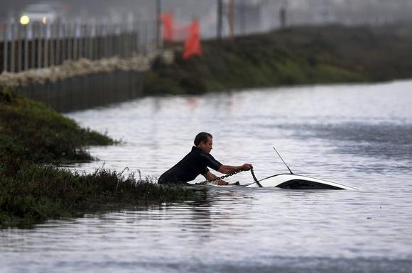 Huntington Beach Marine Safety Officer Claude Panis attaches a chain to hook a tow truck to pull a submerged car from the water at Bolsa Chica Ecological Reserve in Huntington Beach.