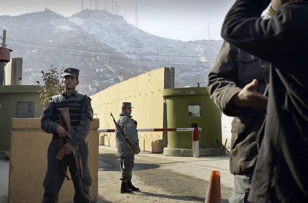 Afghan policemen stand guard outside of Kabul police headquarters, where an American advisor was killed Monday. An Afghan policewoman is suspected in the shooting.