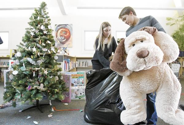 Eighth-graders Kyle McCombs, right, and Tiana Farhang, both 13, help fill trash bags with toys for the Laguna Beach Fire Department's Spark of Love Toy Drive on Dec. 14. Thurston Middle School collected more than 300 toys.
