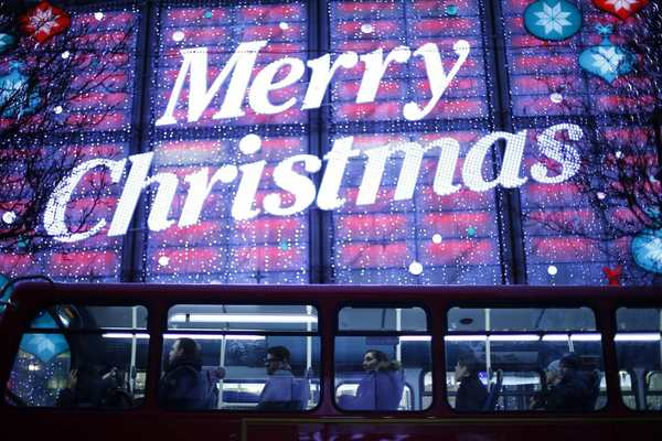 Passengers ride a double decker bus past Christmas lights on Oxford Street, in London, December 24, 2012. British retailers have brought forward their Christmas clearance sales online in the hope that shoppers will log on to buy bargains and offset lackluster spending in stores.
