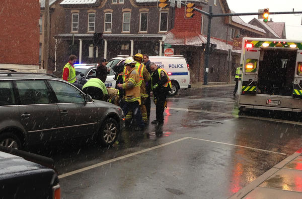 Emergency personnel prepare to place a woman who was struck by a vehicle Monday afternoon at the intersection of Mulberry and Baltimore streets in Hagerstown into an ambulance.