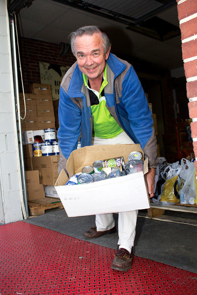 Pastor Harvey Swanger of Cutting Edge Ministries in Hagerstown carries a box of I Care food donations into Raven House Food Center in Hagerstown.