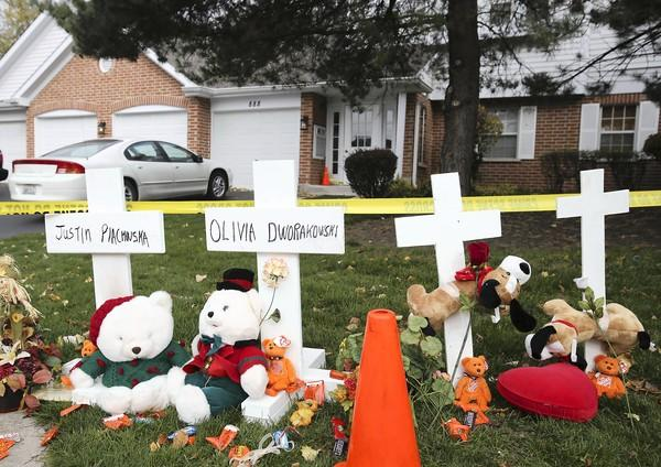 Four wooden crosses mark the house at the scene of the double homicide of two children, five-year-old Olivia Dworakowski and seven-year-old Justin Plackowska, Nov. 1 in Naperville. Two of the crosses are for the two dogs that were also killed. Justin's mother, Elziebta Plackowska has been charged. She had been babysitting at the Dworakowski home.
