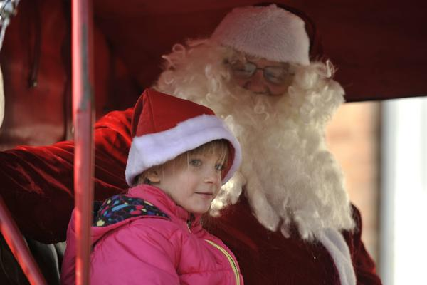 Casey Wehr, 5 1/2 of Frederick, Maryland rides aboard the carriage with Santa. The Allentown Fairgrounds Farmers Market sponsored free horse drawn carriage rides Monday, December 24, 2012 in Allentown, Pennsylvania. Michelle, a Perchron horse that was featured in the movie Elf pulled the carriage owned by Dave McCloughan and Jason Miller of Walnutport.