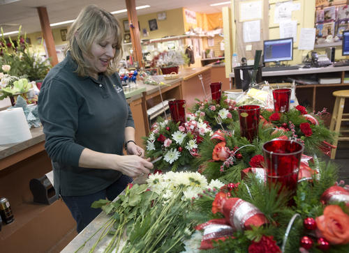 Purchasing Agent Michelle Fagan works on last minute arrangements for delivery Christmas eve at the Phoebe Floral Shop in Allentown around 10 am on Monday. Fagan says that the store has made 1300 deliveries since December 17th.