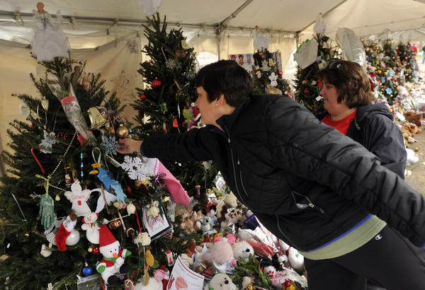 Jackie Fedor of Monroe and her friend Tammie Anastasia of Shelton placed handmade Christmas ornaments on the trees that have been erected as a memorial to the 26 women and children killed at Sandy Hook Elementary School Dec. 14. The friends and Fedor's daughters Michelle and Kathleen helped to make the ornaments and all four were placing them on the trees Christmas Eve in Newtown.