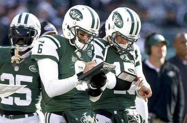 Former starting quarterback Mark Sanchez (6) and reserve Tim Tebow (15) check their playlist during the Jets' game against the Chargers on Sunday.