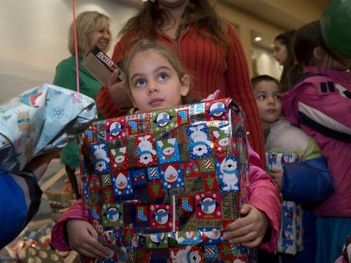 Analyz Bedocs, 5, of Coplay holds onto her gift during the Spirit of the Lehigh Valley at the Holiday Inn Conference Center in Upper Macungie Township on Monday. Spirit of the Lehigh Valley Committee Chairman Brad Mickley says that 350 volunteers staffed the event that served 4000 participants this year. //
