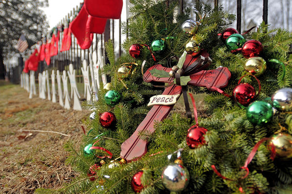 A Christmas wreath leans against a wrought iron fence on Christmas Eve at the Sandy Hook Cemetery along with Christmas stockings and angel cutouts in memory of the 26 women and children killed in the Sandy Hook shootings last week.