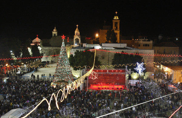 Christian pilgrims and and tourists celebrate Christmas Eve at Manger Square in front of the Church of the Nativity in Bethlehem.
