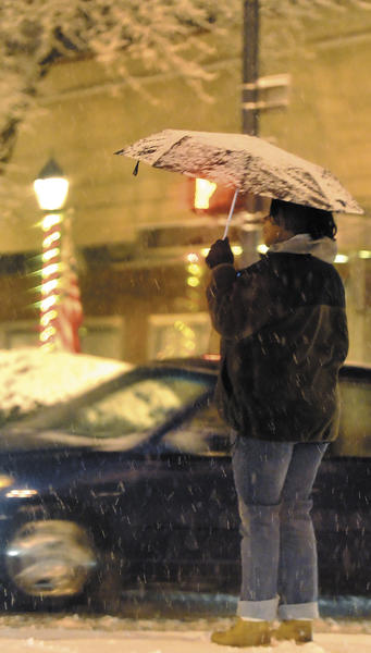 A pedestrian waits to cross Washington Street in downtown Hagerstown during Monday evening's snowstorm.