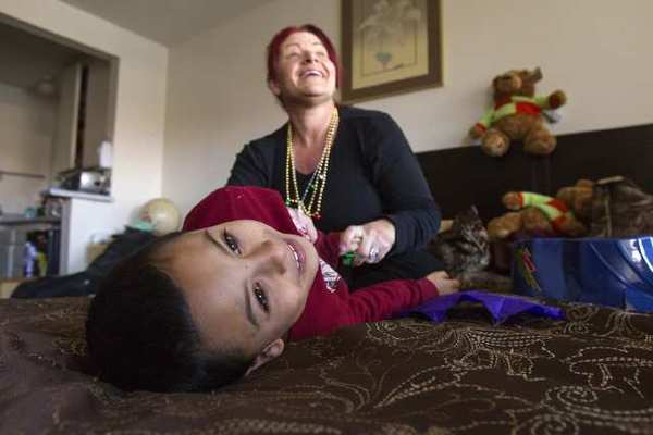 Sonia Rebkowitz plays with her son Johnny Acosta, 7, in their home at the Costa Mesa Motor Inn on Monday.