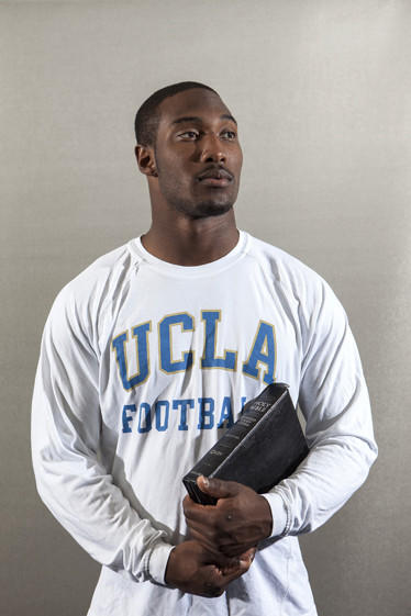 Johnathan Franklin, a senior running back on UCLA's football team, is photographed holding a Bible and football.