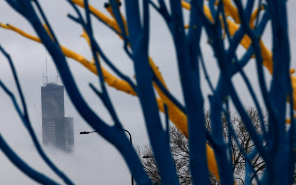 The Willis Tower peeks through as light lake-effect snow falls over Chicago on Christmas.