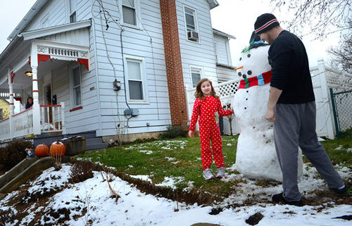 Alana White, 6, and her father Chris White add the finishing touches to a snowman they just built at their home on Roosevelt Street, Whitehall, Tuesday afternoon. Snow that fell on Christmas Eve left the Lehigh Valley area under a white blanket early Christmas Day, 2012.