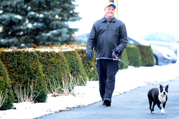 Steve VanNatten of Egypt, Whitehall Twp., walks Lexus, his 2-year-old Boston Terrier, along Hillcrest Lane in Egypt Tuesday afternoon. Snow that fell on Christmas Eve left the Lehigh Valley area under a white blanket early Christmas Day, 2012.