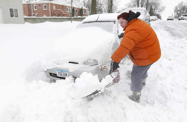 Kimberlee Taylor works to get her car free after a snow plow trapped her car with snow in Cedar Falls, Iowa.