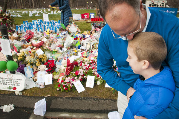At a Sandy Hook memorial in front of St. Rose of Lima Church, Scoop Carlile kisses his son Cooper Carlile, 10, after Cooper placed dozens of cards from his fellow students at Pope John Paul II school in Houston.