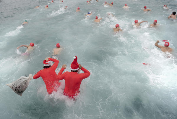 Participants dressed up as Santa Claus jumps in the cold water of Barcelona's Port Vell as he takes part in the103rd edition of the Copa Nadal (Christmas Cup) on December 25, 2012. The traditional 200-meter Christmas swimming race gathered around 400 participants at the Old Harbour of Barcelona. AFP PHOTO / JOSEP LAGO