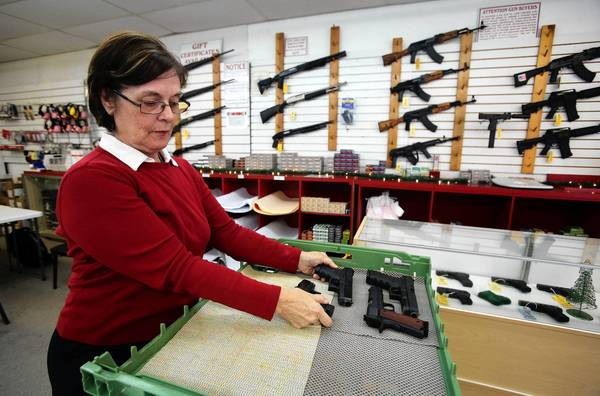 Eileen Rieg demonstrates how her shop's guns are locked away for safety after hours.