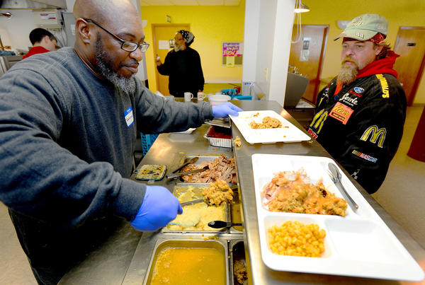 REACH volunteer Terrance Hayward, left, serves a hot Christmas meal to Hagerstown resident Thomas Minnich Tuesday afternoon at REACH. Minnich is a former REACH resident who now lives in Hagerstown and came back to visit the staff and enjoy a meal.