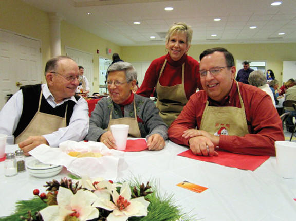 The Townsend family take a break from serving meals at the Asbury United Methodist Church's third annual Community Christmas Dinner in Charles Town, W.Va. From left: Ed and Peggy Townsend from Manchester, Mich., Phyllis Townsend, their daughter-in-law, of Summit Point, W.Va., and her husband, Carl Townsend, of Summit Point.