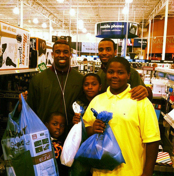 Virginia Tech player Antone Exum, left, treated three children he met at Best Buy to a shopping spree instead of spending the Russell Athletic Bowl gift on himself.
