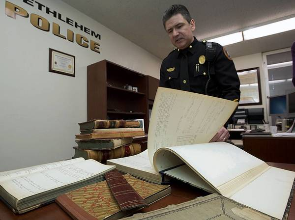 Bethlehem police Deputy Commissioner Craig Finnerty reviews articles and collections of memorabilia in his office at the department's headquarters. The police administration is undergoing a project to preserve the department's history.