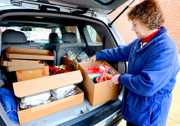 Cathy Melloy of Waynesboro, Pa., packs her car with hot meals and toys Tuesday morning at the Chambersburg (Pa.) Salvation Army and delivered them with her husband Tom Melloy to five families in the Waynesboro area.