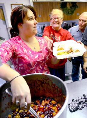 Sabrina Harbaugh, left, hands a container of freshly served hot food to fellow volunteer Debbie Ott, center, for delivery to a Franklin County resident Tuesday morning at the Chambersburg Salvation Army. At right is volunteer Bob Funt.