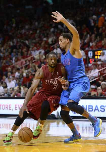 Miami Heat's Dwyane Wade (L) is defended by Oklahoma City Thunder's Perry Jones (R) during the first half of their NBA basketball game in Miami, Florida, December 25, 2012.